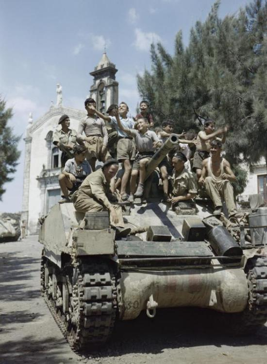 Local_children_crowd_aboard_a_Sherman_Mk_III_tank_of_the_County_of_London_Yeomanry_in_the_village_of_Milo_near_Catania_in_Sicily,_August_1943__TR1244